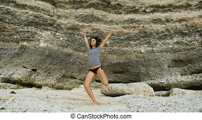Beach on the island of Bali. The girl not tall brunette in a swimsuit. She's in a good mood. Jokes, laughs, jumps and dances posing for the camera. The background of a huge stone wall.