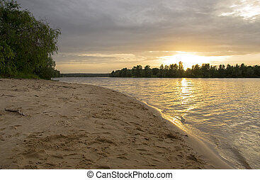 beach on the river at sunset with trees