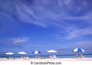 Row of parasols on white sand beach