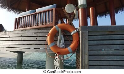 beach patio or terrace with lifebuoy in sea water - travel,...