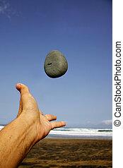 Beach Pebble - Hand throwing pebble on the beach