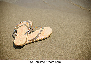 Beach pink flip-flops on a light sand. Texture of light sand. The concept of a beach holiday. Summer shoes. Fashion slaps, Sandals, Summer vacation concept .Copy space