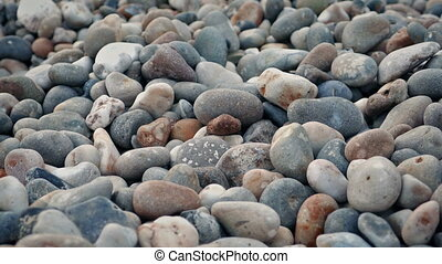 Many smooth rocks on the shore tracking shot