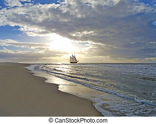 a sailing ship close to the beach in moody sunset