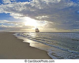 beach, sailing ship, sea and sunset - a sailing ship close...