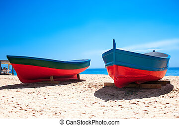 Beach sand, sea and boats in Badalona,  View of the beach with colorful art fishing boats