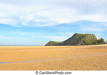 Beach sand with the mountain and blue sky background, at the Pranburi sea in Thailand