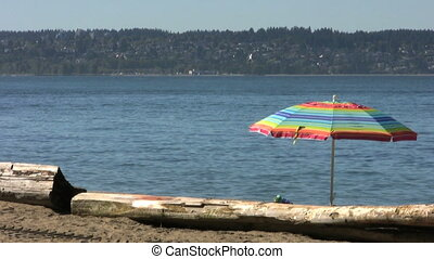 Beach Scene - A rainbow colored umbrella stands by the ocean...