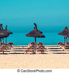 beach scenery with parasol and deck chairs. umbrella and deck chairs