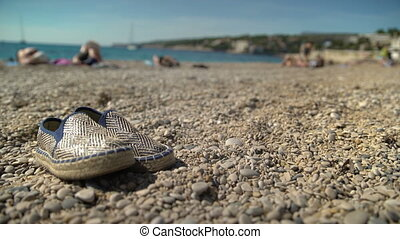Beach Shoes Relax on Rocky Beach - A lonely pair of slippers...