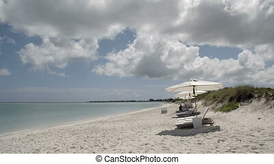 Beach-side view with lounge chairs and umbrellas - A wide...