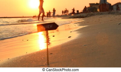 beach sign and the sunset on the sea, vacation, Summertime traveling concept