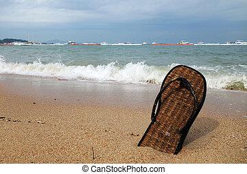 Beach slippers on a sandy beach