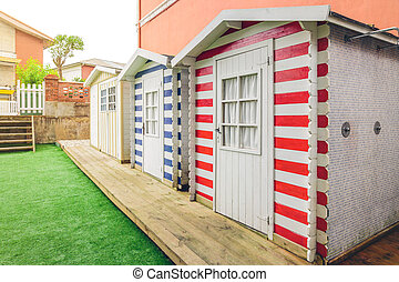 Beach striped huts in a home garden - Row of three colorful...