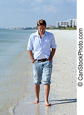 Beach Stroll - Man with rolled jeans walking down beach