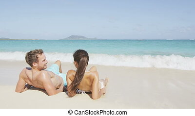 Beach sun tan couple relaxing on holiday in Hawaii. Vacations holidays suntan concept - adults lying down tanning on luxury exclusive beach in Lanikai, Oahu, Hawaii, USA.