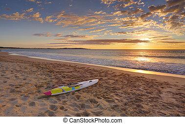 Beach sunrise and paddleboard on shoreline