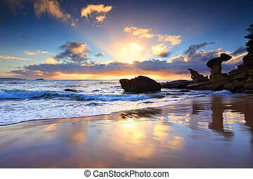 Sunrise at Hargraves Beach Noraville NSW Australia with sunrays sunburst and silhouetted rock formations.