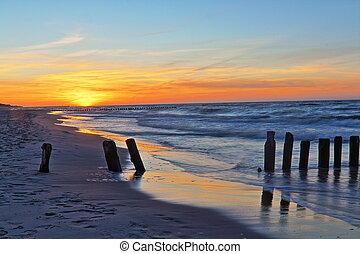 Beach sunset and breakwater