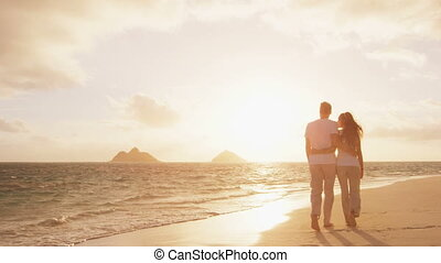 Beach sunset couple walking romantic on honeymoon in love. Sunrise romance young couple in elegant casual clothing walking together enjoying travel vacation holidays.