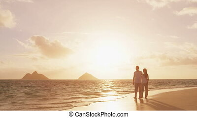 Beach sunset couple walking romantic on honeymoon on Hawaii. Sunrise romance young couple in elegant casual clothing walking together enjoying travel vacation holidays on Lanikai beach, Oahu, USA.