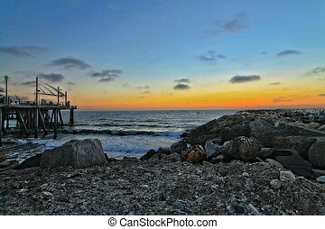 beach sunset with rocks and pier