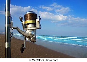 Beach surfcasting spinning fishing reel and rod in tropical...