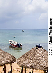 beach thatch roof restaurant huts with fishing boat Caribbean Sea on Little Corn Island Nicaragua Central America