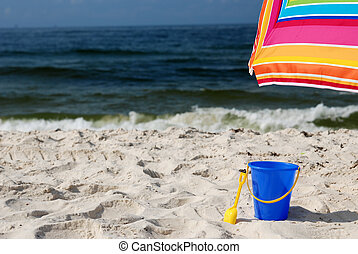 Beach Time - Sand pail and umbrella on white sand beach.