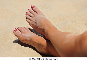 Beach Toes - Tanned, sandy female legs with flowery pink...