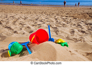 beach toys in sand on sea shore