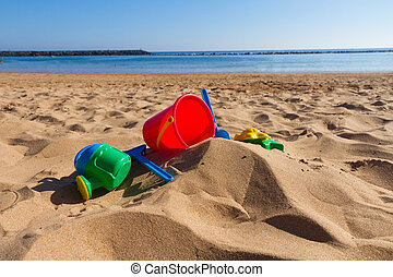 beach toys in sand on sea shore at sunny summer day
