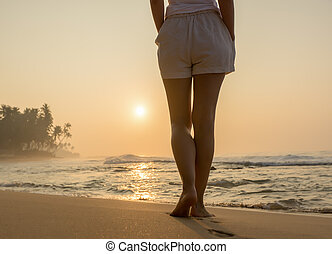 Beach travel - woman walking on sand beach leaving ...