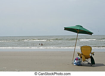 beach umbrella and chair with ocean waves
