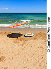 Beach umbrella and toy boat at sea