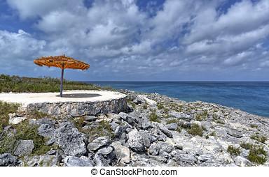 Beach umbrella on a quiet, rocky beach