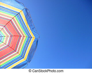 Beach umbrella on blue sky. Summer background with copy space