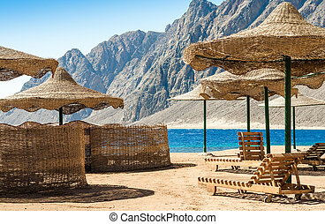 beach umbrellas and wooden lounge chairs on the sand of the beach against the backdrop of the sea and high rocky mountains in Egypt