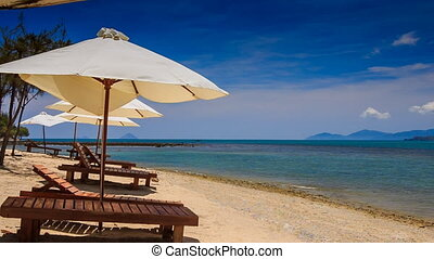 beach umbrellas chairs on gold sand against azure sea