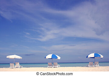 Beach Umbrellas - Three parasols with loungers on empty...