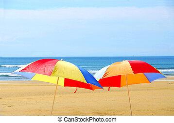 Two beach ubrella standing on ocean shore