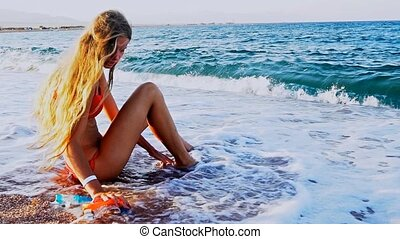 Beach vacation of girl who sitting on sand beach in sea foam wave . Slow motion of blond young woman first time tries herself in snorkeling, is afraid and swears in inept attempts to put on flippers.