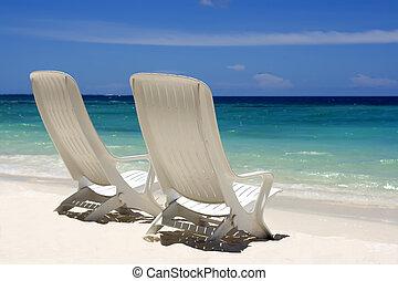 Two beach chairs on a clean, sunny beach. Maldives
