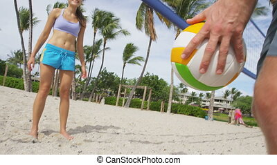 Beach volleyball Friends playing sport having active fun living healthy lifestyle. Man player picking up ball walking during volley ball after game in summer. Woman and man fitness model doing sport.
