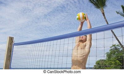 Beach volleyball man playing block blocking volley hitting volley ball during game on summer beach. Male model living healthy active lifestyle doing sport on beach. RED EPIC SLOW MOTION.