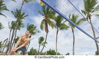 Beach volleyball man playing forearm pass hitting volley ball during game on summer beach. Male model living healthy active lifestyle doing sport on beach. RED EPIC SLOW MOTION.