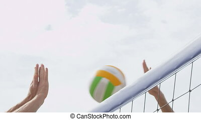 Beach volleyball net closeup spiking and blocking. Man spike smashing and male player with unsuccessful block. People playing volley ball game exercising living healthy sports lifestyle. SLOW MOTION.