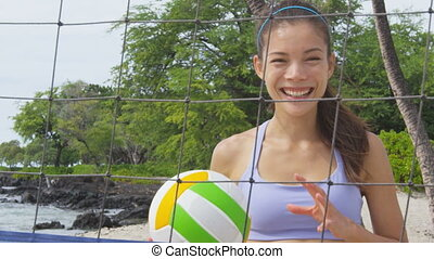 Beach volleyball woman player. Fun Portrait of laughing woman throwing beach volley ball at net and looking at camera. Mixed race Asian Caucasian woman athlete. RED EPIC SLOW MOTION.
