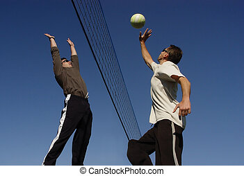 Beach Volleyball - Young men hitting the ball over the net