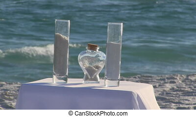 Beach Wedding Sand Ceremony - Two glass containers and a...